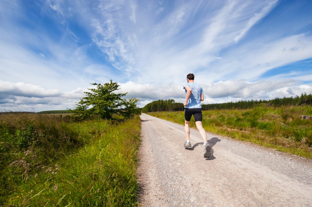 Man running outside in nature for heart health